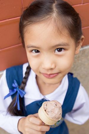 Little Asian cute child enjoy eating ice-cream photo