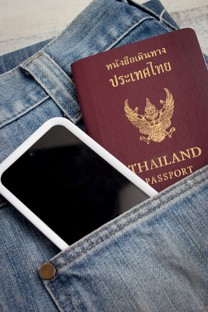 Thai passport in pocket of a jeans with smart phone
