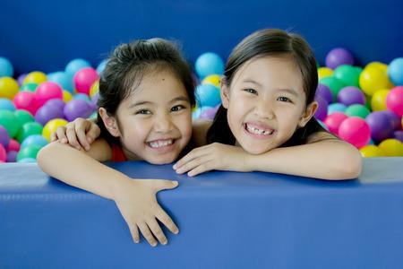カラフルなボールが幼稚園で遊ぶ幸せアジア子供