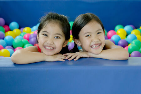 Happy Asian children playing at kindergarten with colorful balls