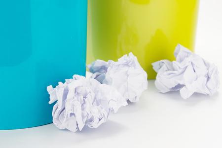 Kleurenafvalbakken en verfrommelde die documenten op witte achtergrond worden geïsoleerd