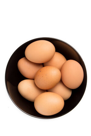 Eggs in the black bowl on isolated background photo