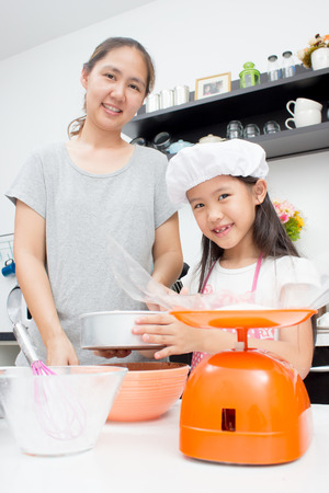 Adorable Asian family baking together in the kitchen photo