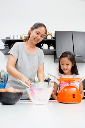 かわいいアジアの家族台所で一緒に焼く