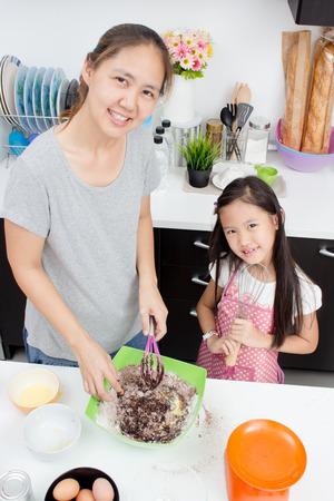 かわいいアジア家族一緒に台所で焼く 写真素材