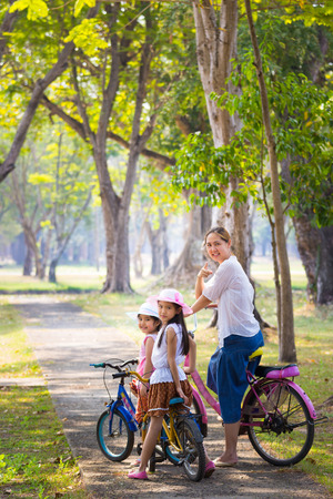 Bike riding - Asian child with mother on bike, active family concept