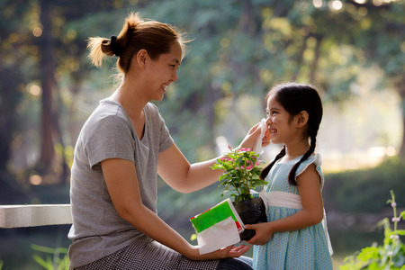 Asian mother cleaning her daughter s face 스톡 콘텐츠