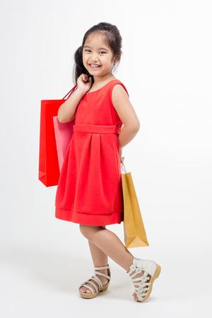 紙の買い物袋を保持している赤いドレス児の小さなアジア