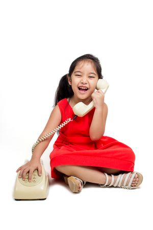 Happy little Asian child in red dress with telephone