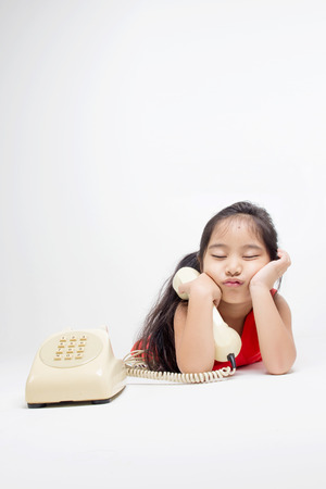 Sleepy Asian child in red dress with telephone photo