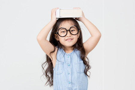 Portrait of little Asian child holding a book on head Stock Photo