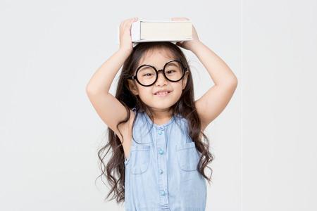 Portrait of little Asian child holding a book on head Stok Fotoğraf