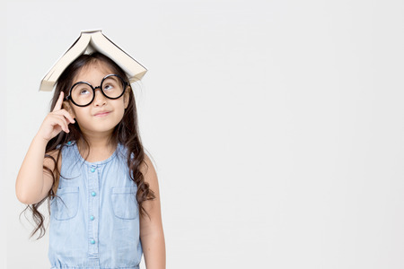 stories: Portrait of little Asian child thinking and put a book on top with copy space Stock Photo