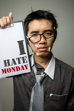 Asian businessman showing board of I hate monday