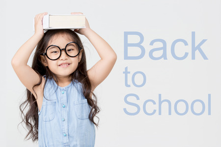 Portrait of little Asian child holding a book on head, Back to school concept  Stock Photo
