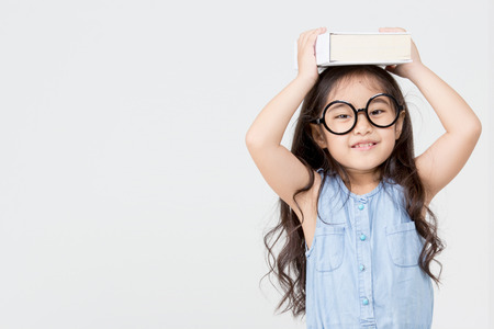 Portrait of little Asian child holding a book on head with copy space