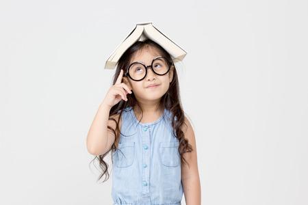 考えて、上に本を置く小さなアジアの子供の肖像画 写真素材