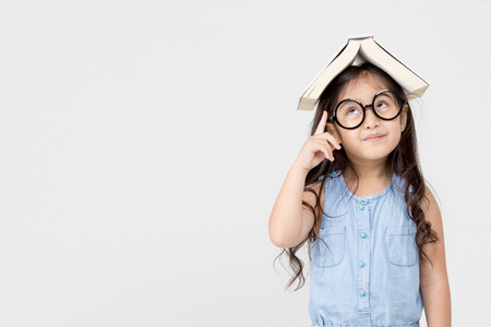 Portrait of little Asian child thinking and put a book on top with copy space Foto de archivo