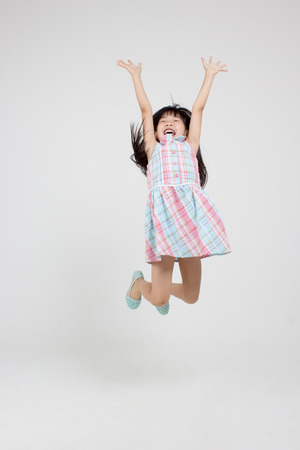 Portrait of happy little Asian child jumping Stock Photo - 33632246
