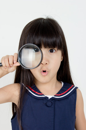 Portrait of happy little Asian child with magnifying glass 스톡 콘텐츠