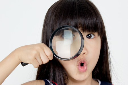 Portrait of happy little Asian child with magnifying glass Stock Photo