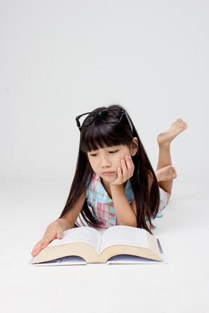 Portrait of little Asian child reading a book on the floor Stock Photo