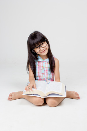Portrait of little Asian child reading a book