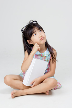 Portrait of little Asian child thinking and holding a book