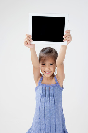 Happy Asian child holding tablet computer photo
