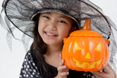 Portrait of little Asian girl in black hat and black clothing with pumpkin Stock Photo