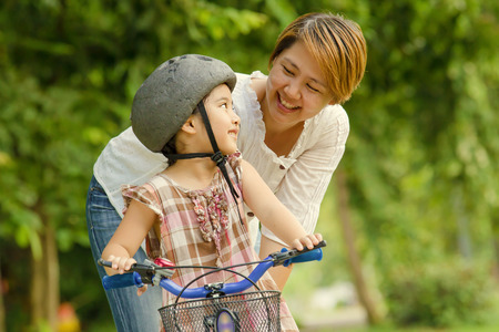 Little Asian child with mother practice to riding a bicycle Stock Photo - 33135830
