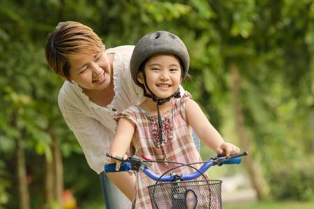 ni�os sonriendo: Ni�o asi�tico peque�o con la pr�ctica de la madre al andar en bicicleta Foto de archivo