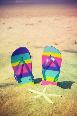 flops: Vintage of colorful flip-flops on sand beach Stock Photo