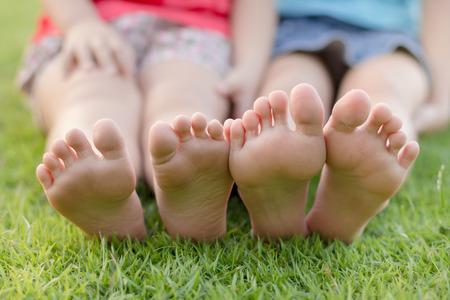 裸足の芝生に座って幸せな子