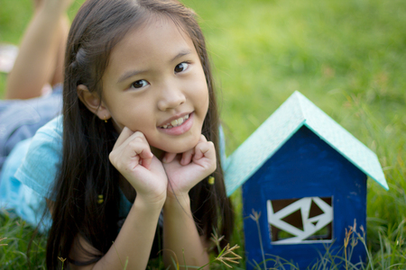 Little Asian child lying on the grass with house toy