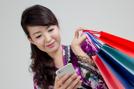 Asian woman using smart phone and holding colorful shopping bags