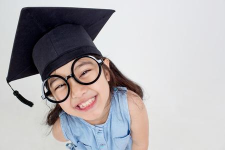 Happy Asian school kid graduate in graduation cap with copy space Stok Fotoğraf