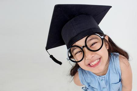 Happy Asian school kid graduate in graduation cap with copy space 스톡 콘텐츠