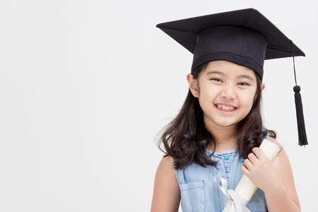 graduacion: Graduado asi�tico ni�o feliz de la escuela en la tapa de graduaci�n