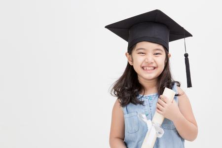 Happy Asian school kid graduate in graduation cap photo