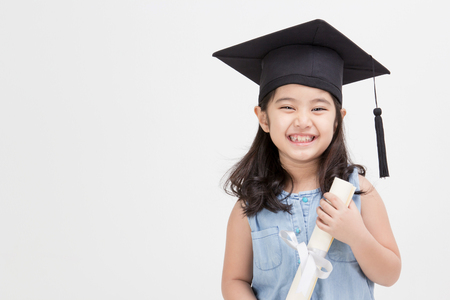 Happy Asian school kid graduate in graduation cap Stock Photo - 35886369