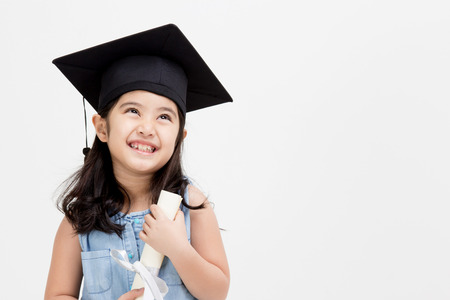 education kids: Happy Asian school kid graduate in graduation cap looking up