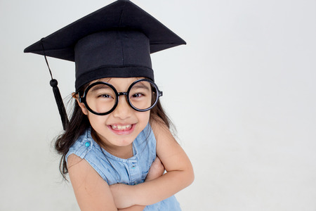 Happy Asian school kid graduate in graduation cap with copy space Stock Photo