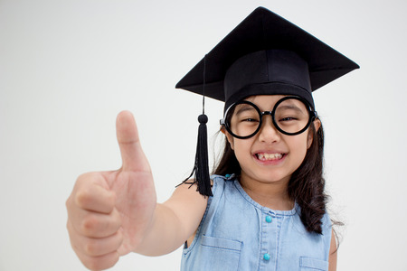 Happy Asian school kid graduate in graduation cap with big thumb up 스톡 콘텐츠