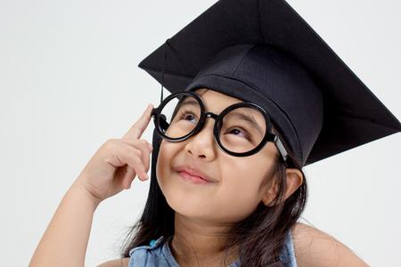 Happy Asian school kid graduate thinking with graduation cap photo