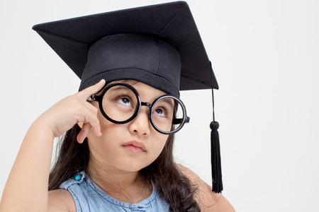 Happy Asian school kid graduate thinking with graduation cap Stock Photo - 35114187