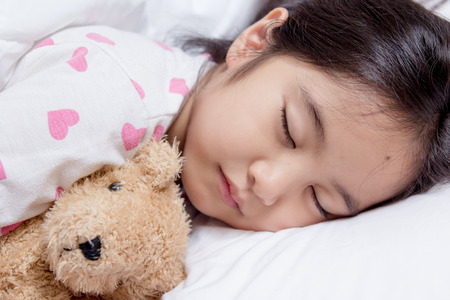 Lovely Asian child laying down on the bed Stock Photo