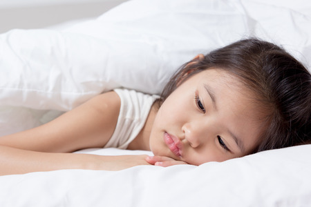 Little Asian child has fever and laying on the bed 스톡 콘텐츠