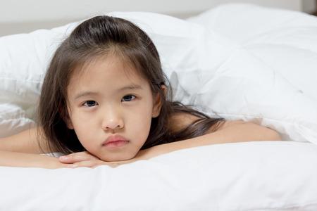 ragazza malata: Piccolo bambino asiatico ha la febbre e posa sul letto Archivio Fotografico