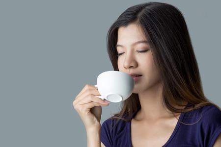 コーヒーを飲みながら美しいアジアの少女 写真素材